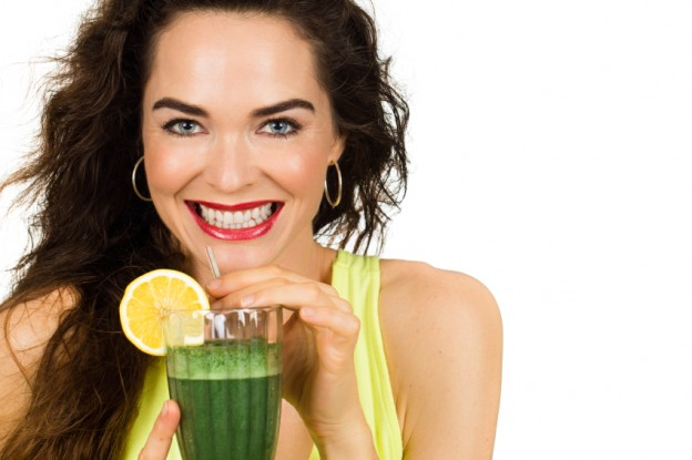 Woman about to drink a green smoothie.